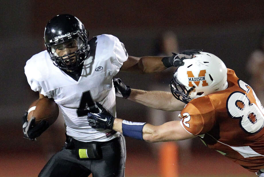 Steele's Justin Stockton (04) pushes off a tackle by Madison's Mitchell Brown (82) in the second half at Heroes Stadium on Friday, August 31, 2012. Photo: Kin Man Hui, Express-News / ©2012 San Antonio Express-News