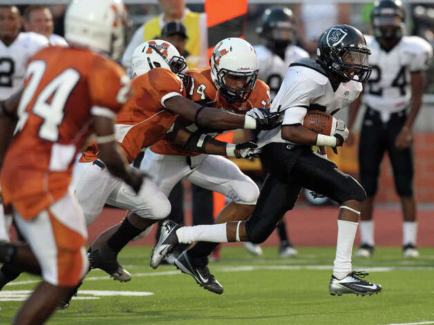 Steele's D'Angelo Wallace (21) attempts to break the grasps of Madison's Marquis Warford (04) and Lavelle Delahoussaye (14) in the first half at Heroes Stadium on Friday, August 31, 2012. Photo: Kin Man Hui, Express-News / ©2012 San Antonio Express-News