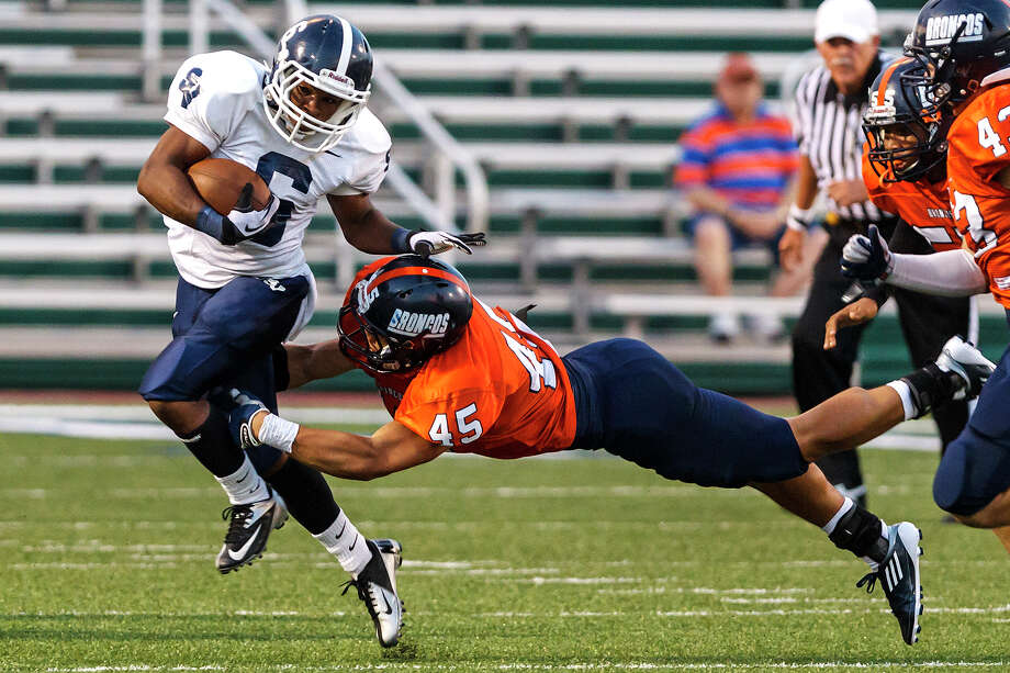 Brandeis linebacker Chase Guillory (center) makes a flying tackle on Smithson Valley's Xavier Coombs during the first half of the season opener for both teams at Farris Stadium on Aug. 31, 2012.  Smithson Valley won the game 41-7.  MARVIN PFEIFFER/ mpfeiffer@express-news.net Photo: MARVIN PFEIFFER, Express-News / Express-News 2012
