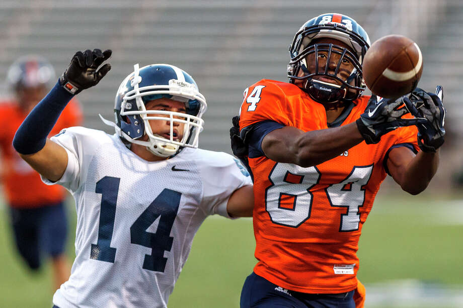 Brandeis wide receiver Larry Stephens tries to haul in a pass as Smithson Valley's Carlos Castello closes in during the first half of the season opener for both teams at Farris Stadium on Aug. 31, 2012.  Smithson Valley won the game 41-7.  MARVIN PFEIFFER/ mpfeiffer@express-news.net Photo: MARVIN PFEIFFER, Express-News / Express-News 2012