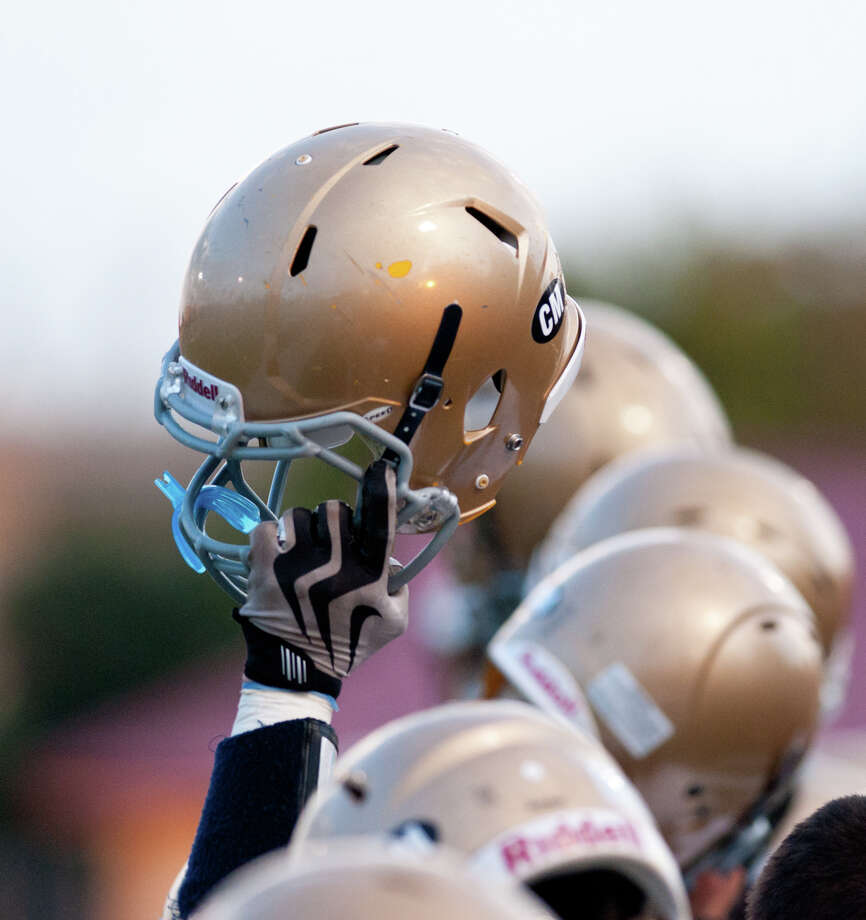 Holy Cross players raise their helmets prior to their game against Central Catholic. Photo: Express-News