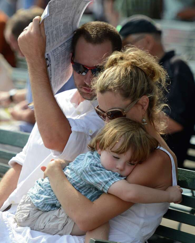 Little Mason Stanco, 4 catches a few needed moments of sleep in his mother Julie Stanco's arms as dad Paul Stanco uses a race program for shade at the Saratoga Race Course in Saratoga Springs, N.Y.  Aug. 31, 2012.   (Skip Dickstein/Times Union) Photo: Skip Dickstein