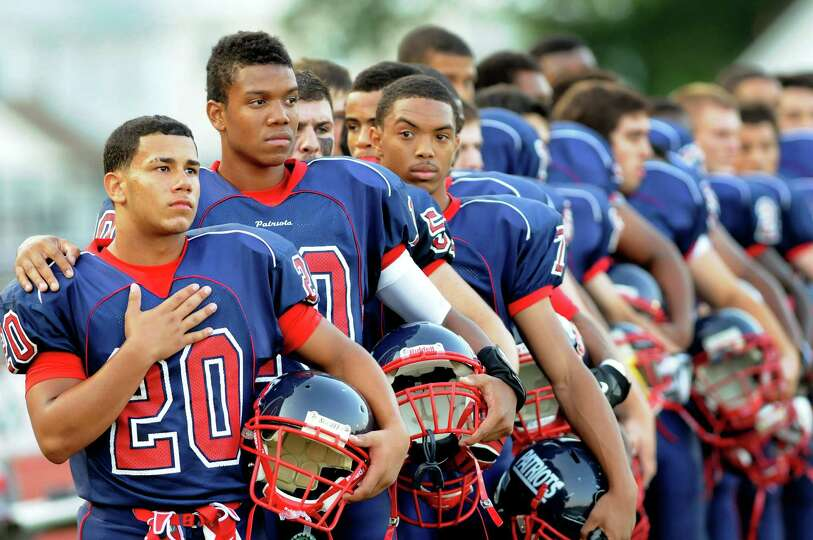 Schenectady's running back Felix Rodriguez (20), left, quarterback Kwame Jarvis (10) join the team d