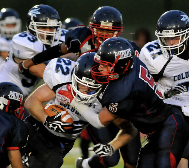 Columbia's Chris Smith (22), center, leans into a tackle by Schenectady's Jeremy Kent (5) during the