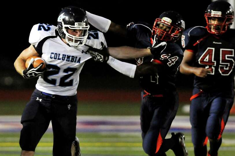 Columbia's running back Chris Smith (22), left, stiff arms Schenectady's Nakia Boozer (44) during th