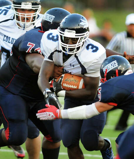 Columbia's running back Kenny Mathieu (3), center, runs into heavy traffic during their football gam