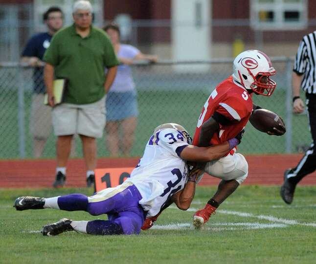 Christian Brothers Academy's Cameron Wynn (34) tackles Guilderland's Micaiah Henningham (5) during t
