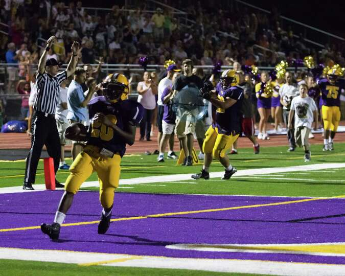 Troy High player #20 runs the ball into the end zone for the first touchdown of the game against Bur
