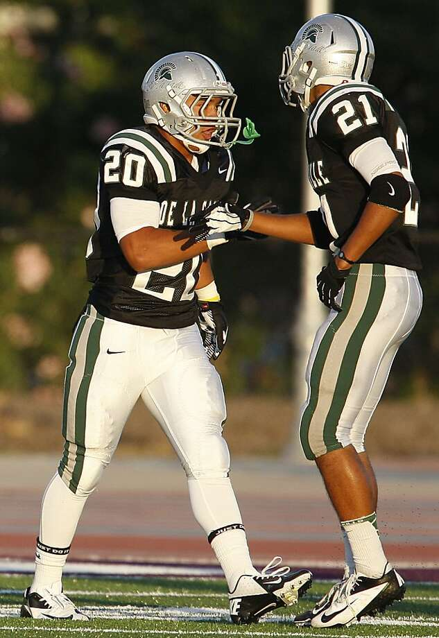 Pepe Vitale (left), greeted by teammate Das Tautalatasi, rolled for 180 yards and three TDs. Photo: Liz Hafalia, The Chronicle