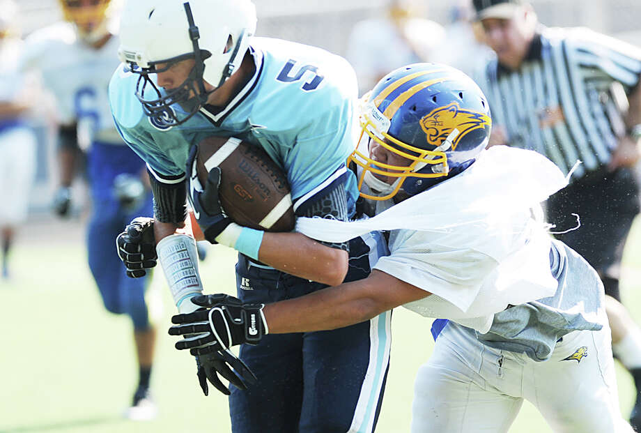 Wilton's Zack Laurinaitis, left, # 5, is tackled by a Brookfield High School player during the high School football jamboree at Wilton High School, Saturday morning, Sept. 1, 2012. Photo: Bob Luckey / Greenwich Time