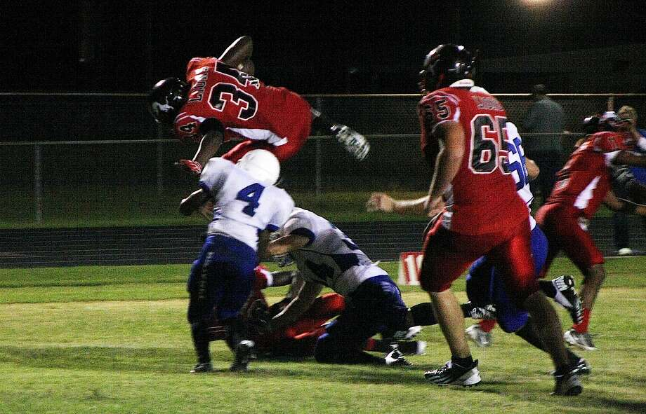 The Kountze Lions opened their 2012-13 football season with an exciting, hard hitting game against the Shepherd Pirates. When the final seconds ticked off the clock, Kountze was on top 43-35. Javonte Powell leaps over Pirate defenders to score a 2-point conversion in the Lion win. Photo: David Lisenby, Freelance