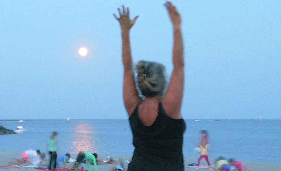 "A yoga session was staged Friday night -- under a full ""blue"" moon -- on Jennings Beach by Yoga for Everybody. Photo: Mike Lauterborn / Fairfield Citizen contributed"
