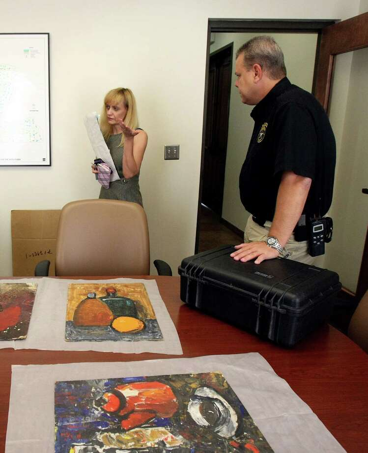 Liza Rukhina speaks with Olmos Park police officers, including Senior Sgt. Joe Schutze. Most of the artwork taken from her residence has been returned to her. Photo: Helen L. Montoya, San Antonio Express-News / ©SAN ANTONIO EXPRESS-NEWS