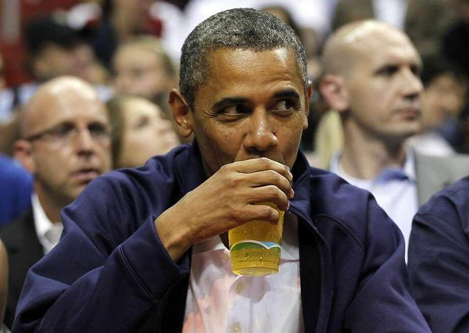 FILE - In this July 16, 2012 file photo, President Barack Obama sips his beer as he watches Team USA and Brazil during the first half of an Olympic men's exhibition basketball game, in Washington. Obama and his team frequently talk about the president's fondness for beer, and Obama has been photographed many times downing a beer, including an appearance at the Iowa State Fair last month. Being identified as a beer drinker is an easy way for Obama to connect with votes and serves as a not-so-subtle reminder that his Republican rival Mitt Romney, a Mormon, doesn't drink. (AP Photo/Alex Brandon, File) Photo: Alex Brandon, Associated Press