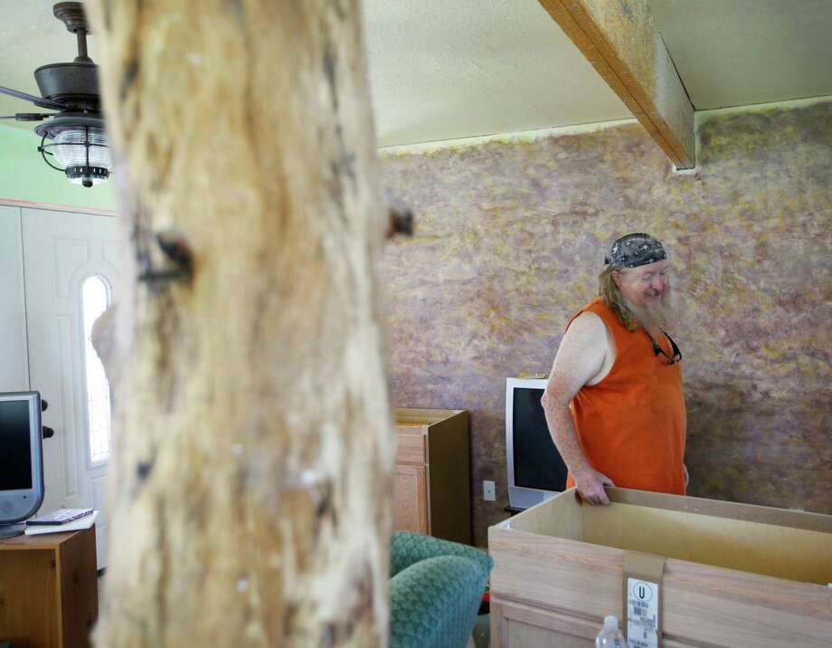 Michael Hritz is still at least a year from moving into his house, where a tree trunk with one burned spot (foreground) serves as a support beam in his new living room. Photo: William Luther, San Antonio Express-News / © 2012 San Antonio Express-News
