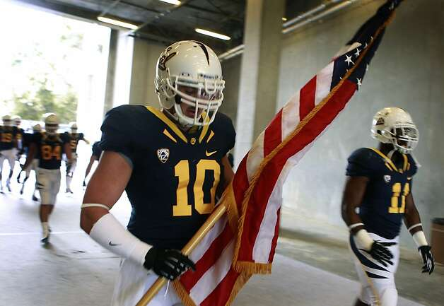 Linebacker Lucas King carries the American flag before leading teammates onto the field for the first Cal Bears game at the renovated Memorial Stadium against the Nevada Wolfpack in Berkeley, Calif. on Saturday, Sept. 1, 2012. Photo: Paul Chinn, The Chronicle