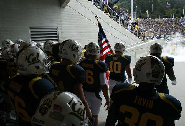 Linebacker Lucas King (10) carries the American flag before leading teammates onto the field for the first Cal Bears game at the renovated Memorial Stadium against the Nevada Wolfpack in Berkeley, Calif. on Saturday, Sept. 1, 2012. Photo: Paul Chinn, The Chronicle