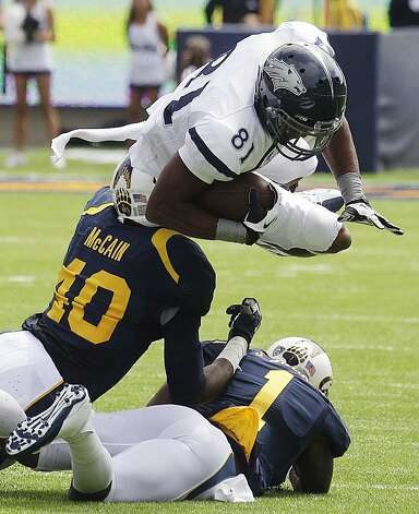 Nevada's Aaron Bradley (81) dives over California's Chris McCain (40) and Steve Williams (1) during the first half of an NCAA college football game, Saturday, Sept. 1, 2012, in Berkeley, Calif. (AP Photo/Ben Margot) Photo: Ben Margot, Associated Press