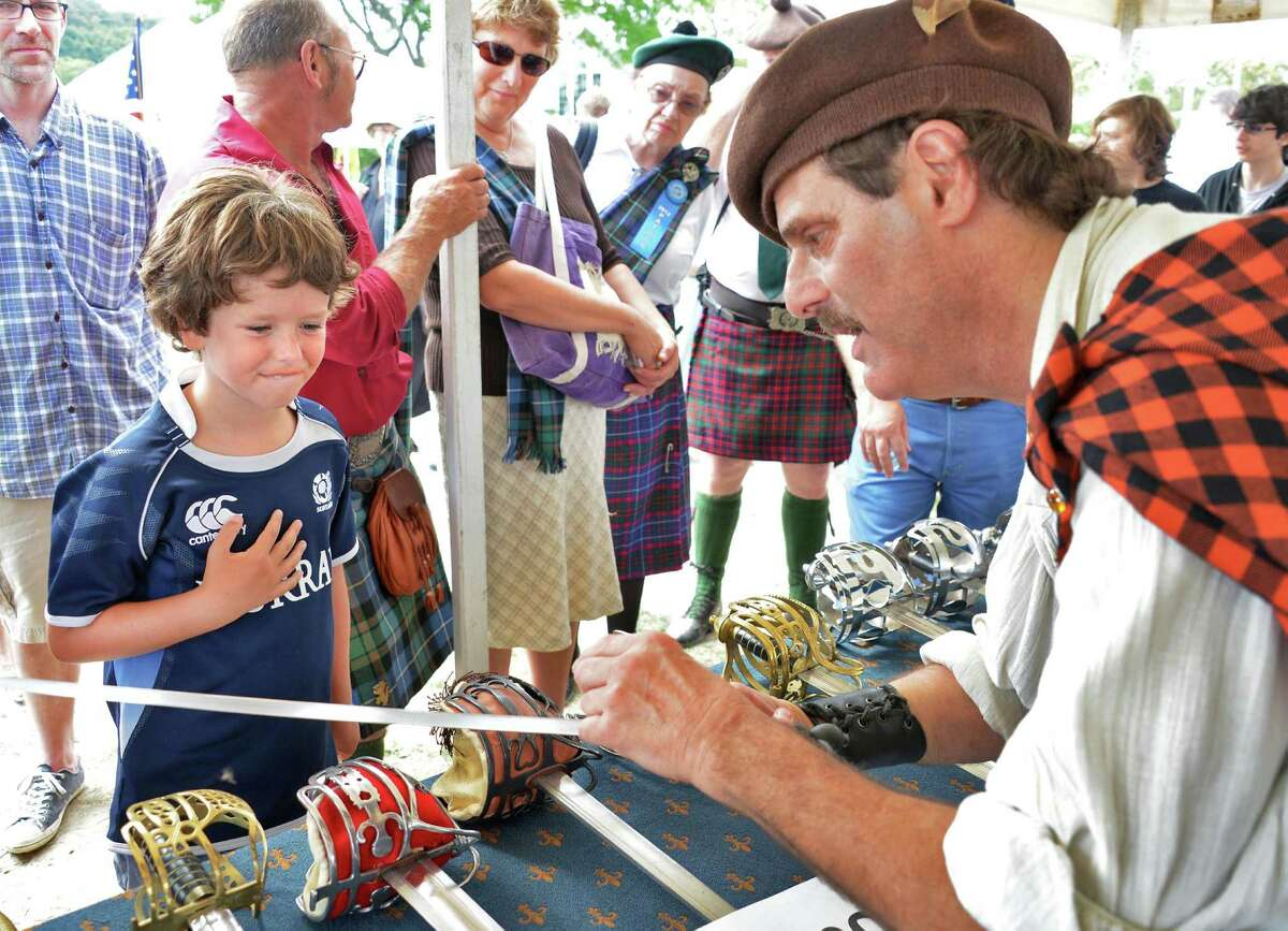 """Carter Gemmell, 8, of Saratoga Springs, left, gets a close up look at the sword of Capt. Jack Sparro of """"Pirates of the Carribean"""" from Scott Ian Barry during a living history of the sword presentation during the Scottish Games at the Altamont Fairgrounds Saturday Sept. 1, 2012. (John Carl D'Annibale / Times Union)"""