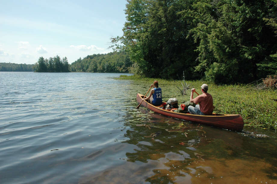 "In this Aug. 25, 2012 photo, Leah and Bruce Nelson, of Albany, N.Y., paddle a canoe loaded with camping gear onto Floodwood Pond in the Saranac Lakes Wild Forest at Saranac Lake, N.Y. A new guidebook, ""Adirondack Paddling: 60 Great Flatwater Adventures,"" is due out this year, aimed at the growing number of people exploring the expanding opportunities for paddlers in the Adirondack Park. (AP Photo/Mary Esch) Photo: Mary Esch"