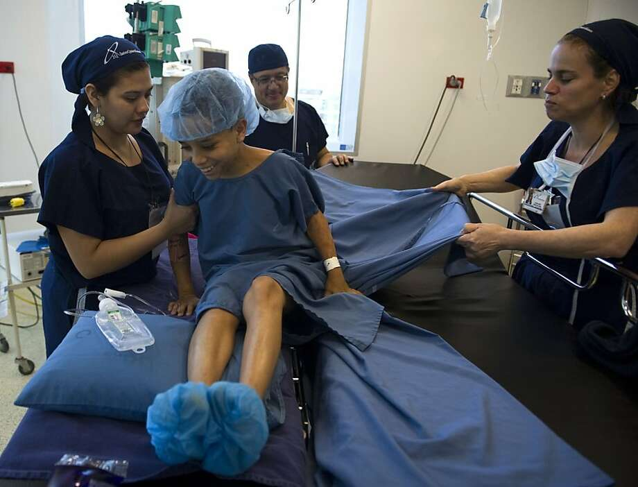 Nurses prepare Juan Diego Zuluaga, 14, for his scar correction operation on September 1, 2012, in a clinic in Medellin, Antioquia department, Colombia. Colombian doctors operated for free 111 poor children from hearing problems, burns and harelip among other illnesses, during the Children's Day Surgeries --an event organized by the mayor's office and a doctors' association to improve the children's quality of life and health conditions.   AFP PHOTO/Raul ARBOLEDARAUL ARBOLEDA/AFP/GettyImages Photo: Raul Arboleda, AFP/Getty Images
