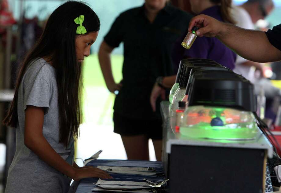 Nine-year-old Nicole Tom looks over Rainmate Air Purifier during the annual Aloha TexFest at Clear Lake Park Saturday, Sept. 1, 2012, in Seabrook. Photo: James Nielsen, Chronicle / © Houston Chronicle 2012
