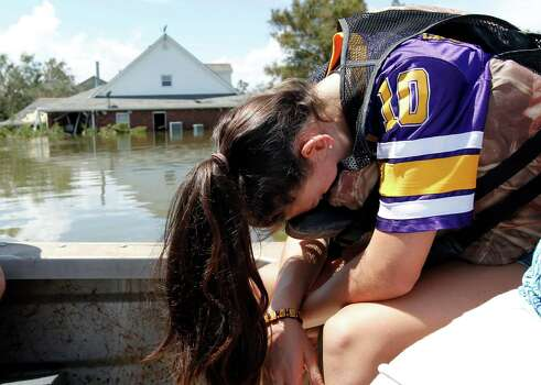 Lainy Serpas, 11, lowers her head into her lap as she tours her flooded community for the first time, after Hurricane Isaac passed through in Braithwaite, La., Saturday, Sept. 1, 2012. Photo: Gerald Herbert, Associated Press / AP