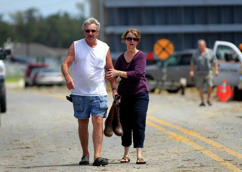 Richard and Mary Williams approach their flooded community after walking through the now open flood