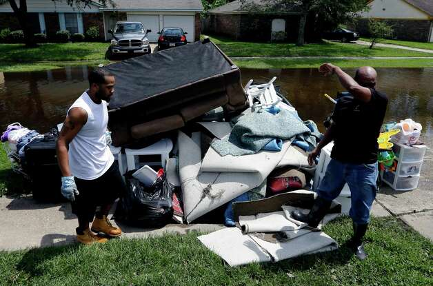 Deron Dumes, left, and his uncle Greg Dumes remove damaged item from their flood damaged home in the aftermath of Hurricane Isaac in LaPlace, La., Saturday, Sept. 1, 2012. Floodwaters cover many streets and power remains out in some areas. Photo: David J. Phillip, Associated Press / AP