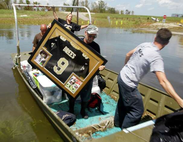 Russell Wilson unloads a water damaged Drew Brees signed shirt for his daughter Amy Keller and her husband Michael from their  Braithwaite, La. home, Saturday September 1, 2012. It was the first time the Keller family was able to get tho their flooded home since Hurricane Isaac storm surge inundated the area. Photo: David Grunfeld, Associated Press / THE TIMES-PICAYUNE