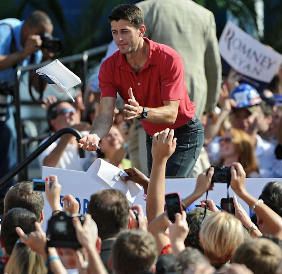 A member of the audience tosses a book to vice presidential candidate, Rep. Paul Ryan, R-Wis. for his autograph as the rally ends, Saturday, Sept. 1, 2012 in Jacksonville, Fla. (AP Photo/The Florida Times-Union, Bob Mack) TV OUT; MAGS OUT