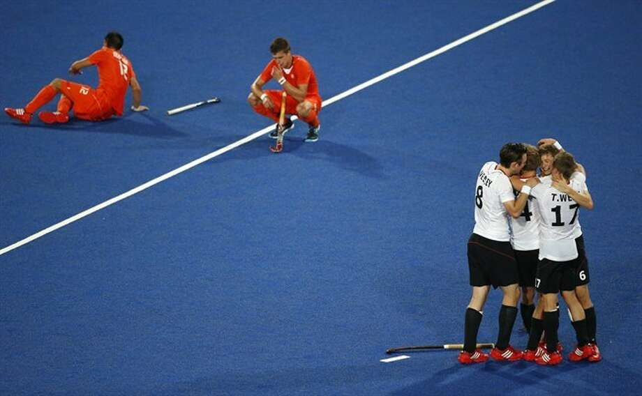 A group of German players celebrate their team's 2-1 win against the Netherlands after the men's field hockey gold medal match at the 2012 Summer Olympics, in London, Saturday, Aug. 11, 2012. (AP Photo/Jae C. Hong)