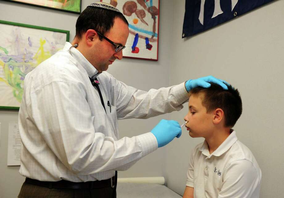 Dr. Nimrod Dayan administers a flu shot to eleven-year-old Chris Parkin Thursday, August 30, 2012 at Pediatric Healthcare Associates in Trumbull.  Dayan, whose specialty is Pediatric Infectious Disease, feels strongly about the importance of vaccinations. Photo: Autumn Driscoll / Connecticut Post