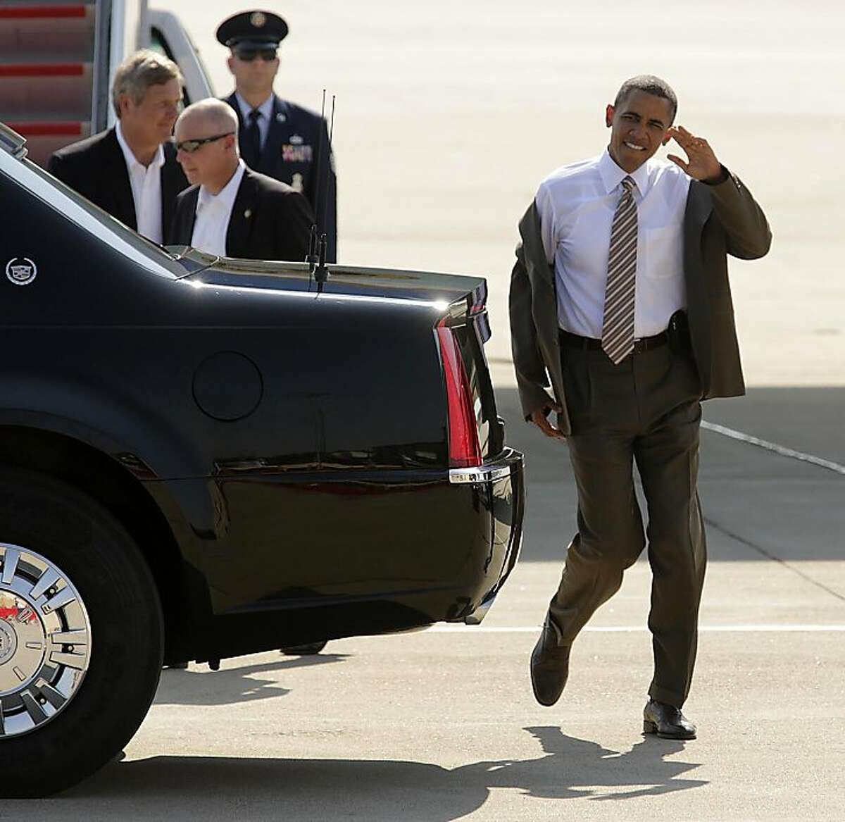 President Barack Obama shrugs his coat off as he waves to supporters after arriving at the Sioux Gateway Airport in Sioux City, Iowa, Saturday, Sept. 1, 2012, to attend a rally at Morningside College in Sioux City. (AP Photo/Jerry Mennenga)