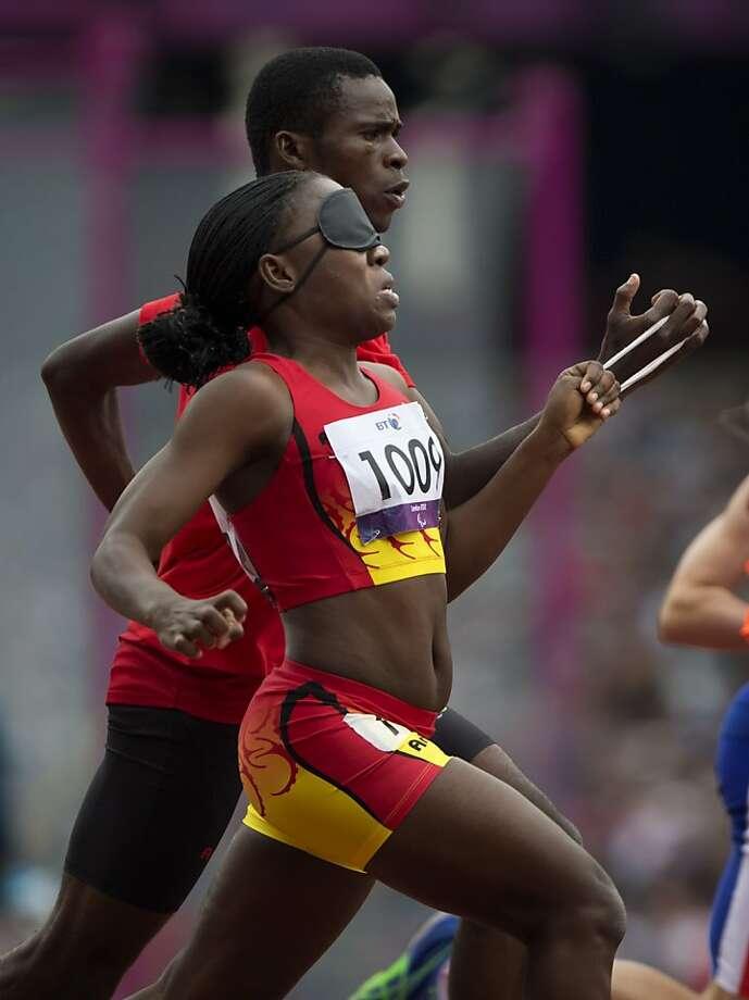 Angola's Esperanca Gicaso runs blindfolded next to her guide Maracio Jose Fonseca Neto during the Women's 200 metre T11 at the 2012 Paralympics in London, Saturday, Sept. 1, 2012. (AP Photo/Emilio Morenatti) Photo: Emilio Morenatti, Associated Press
