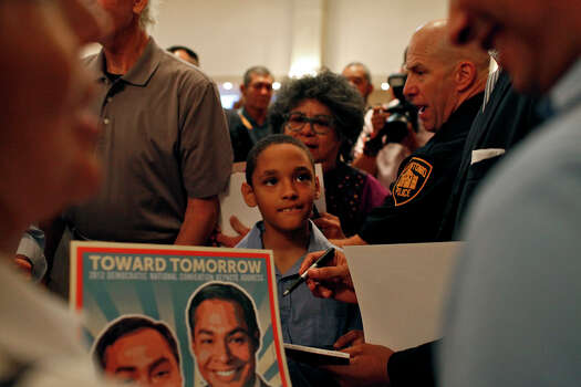 Louis Harrison, 8, center, waits to get autographs from Mayor Julián Castro, and his brother, Joaquín Castro, right, during the send-off party for their trip to the Democratic National Convention at the St. Paul Community Center in San Antonio on Saturday, Sept. 1, 2012. Photo: Lisa Krantz, San Antonio Express-News / San Antonio Express-News