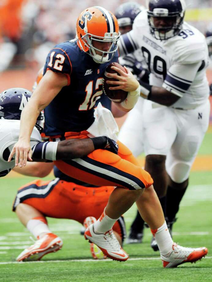 Syracuse quarterback Ryan Nassib (12) runs for a first down against Northwestern during the first quarter of an NCAA college football game in Syracuse, N.Y., Saturday, Sept. 1, 2012. (AP Photo/Hans Pennink) Photo: Hans Pennink