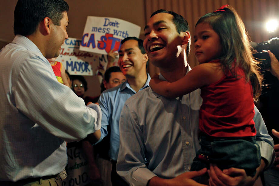 Mayor Julián Castro, holding daughter Carina, and state Rep. Joaquín Castro greet supporters at the sendoff party. Photo: Lisa Krantz, San Antonio Express-News / San Antonio Express-News