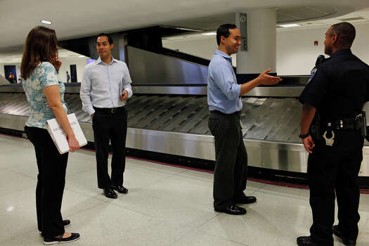 Mayor Julián Castro, left, and his brother, Joaquín Castro, right, wait for their luggage upon their arrival in Charlotte, NC, for the Democratic National Convention on Saturday, Sept. 1, 2012. Photo: Lisa Krantz, San Antonio Express-News / San Antonio Express-News