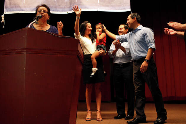 Choco Meza, left, introduces the Castro family including Mayor Julian Castro, center, his wife, Erica Castro, their daughter, Carina, 3, and his brother, Joaquin Castro, right, during the send-off party for their trip to the Democratic National Convention at the St. Paul Community Center in San Antonio on Saturday, Sept. 1, 2012. Photo: Lisa Krantz, San Antonio Express-News / San Antonio Express-News