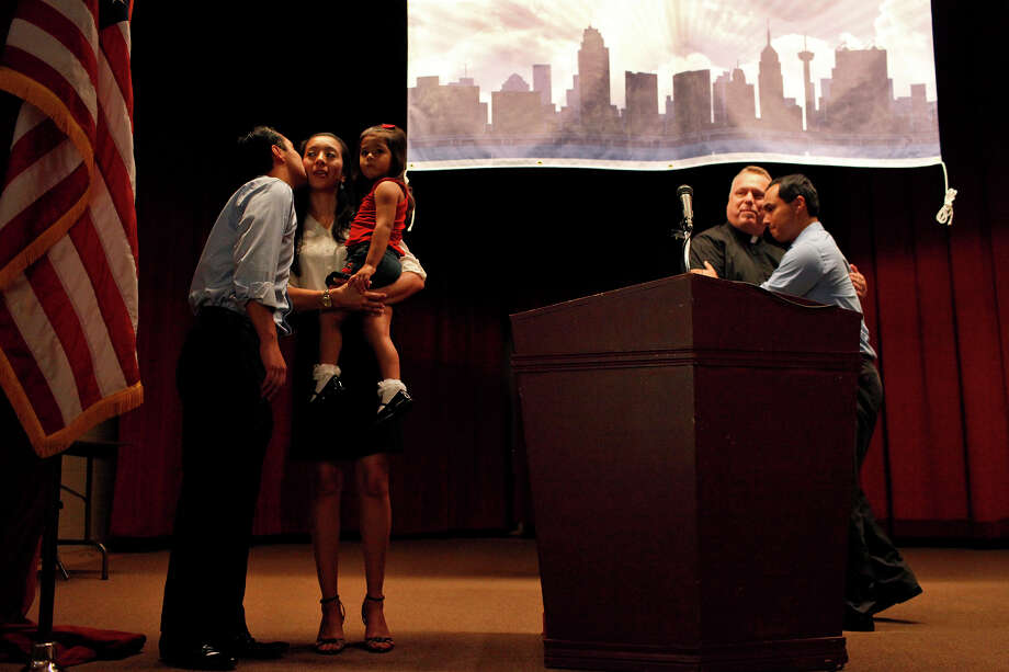 Mayor Julian Castro kisses his wife, Erica, with their daughter, Carina, 3, as his brother, Joaquin Castro, right, embraces Father Jimmy Drennan during the send-off party for their trip to the Democratic National Convention at the St. Paul Community Center in San Antonio on Saturday, Sept. 1, 2012. Photo: Lisa Krantz, San Antonio Express-News / San Antonio Express-News