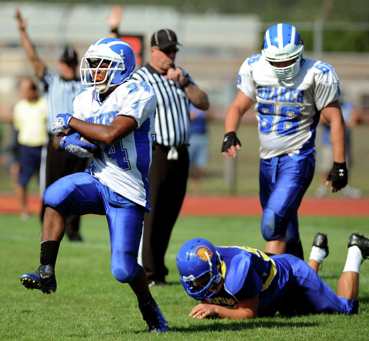 Shaker's Kenny Jackson (34), left, dodges a tackle and scores a touchdown during their football game against Queensbury on Saturday, Sept. 1, 2012, at Queensbury High in Queensbury, N.Y. (Cindy Schultz / Times Union)