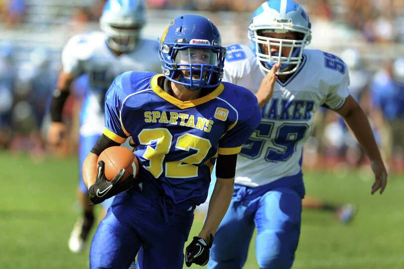 Queensbury's Timothy Voorhis (32), center, out runs Shaker's Phil Cuen (59) and carries the ball int