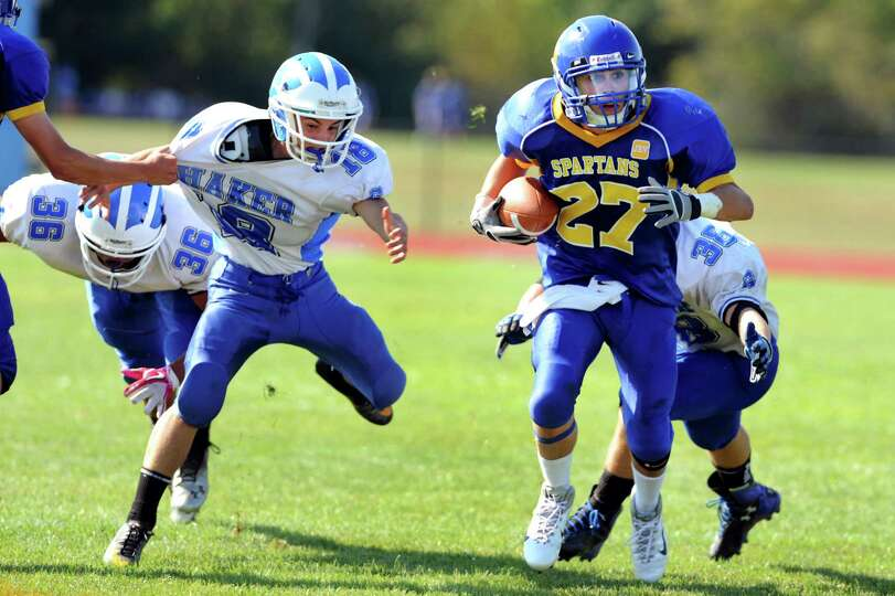 Queensbury's Timothy Voorhis (27), right, gets ahead of Shaker's defense during their football game