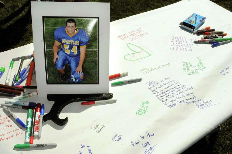 A picture of Queensbury Johnathan Vasiliou graces a banner for attendees to sign during their footba