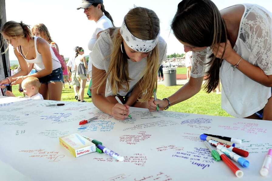 Students Madeleine Brilling, 15, center, and Christie Raymond, 15, right, sign a banner in remembran