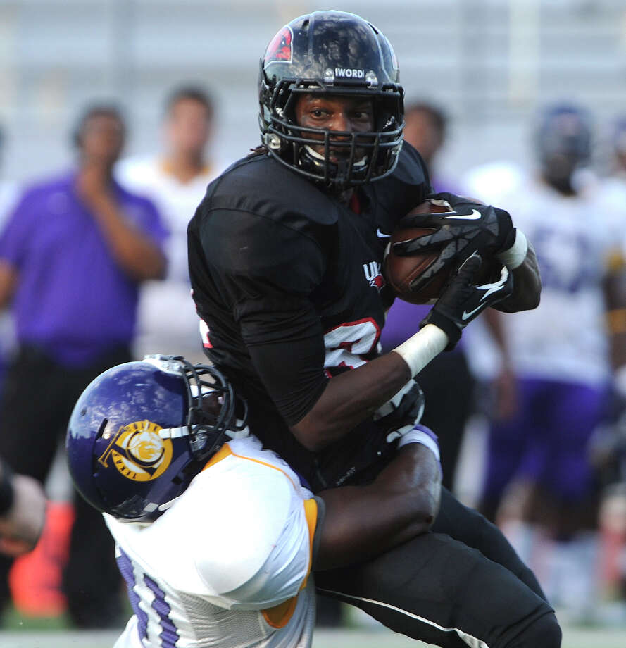 Receiver Kent Hadnot of Incarnate Word is tackled by Demanuel Bailey of Texas College during action at Benson Stadium on Saturday, Sept. 1, 2012. Photo: Billy Calzada, Express-News / © San Antonio Express-News