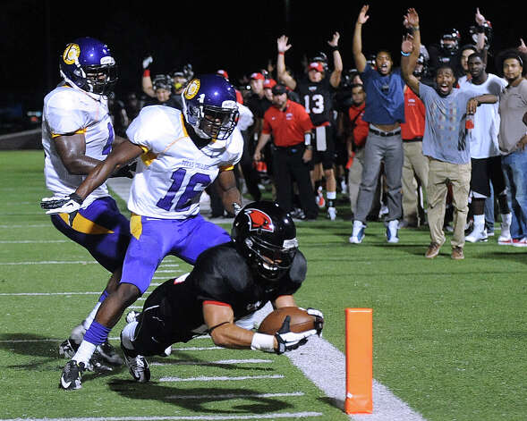 Incarnate Word running back Trent Rios dives into the end zone for a third-quarter touchdown ahead of Devonte Mooris (16) of Texas College during football action at Benson Stadium on Saturday, Sept. 1, 2012. Photo: Billy Calzada, Express-News / © San Antonio Express-News