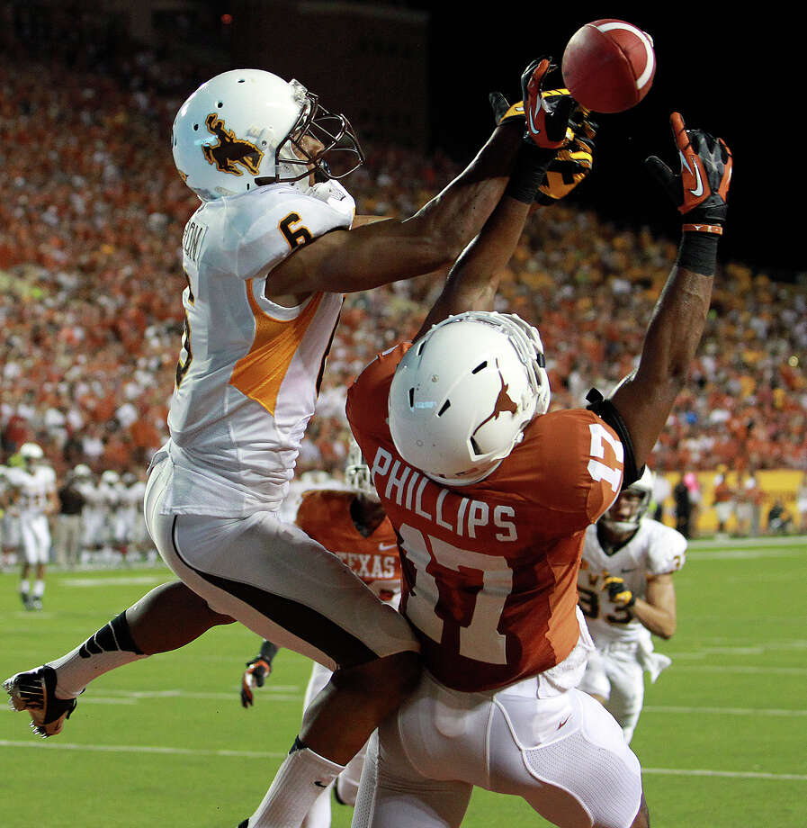 Longhorn defender Adrian PhilipsTbreaks up a pass to Robert Herron in the fourth quarter as Texas hosts Wyoming at D.K.Royal Stadium in Austin on September 1, 2012. Photo: Tom Reel, Express-News / ©2012 San Antono Express-News