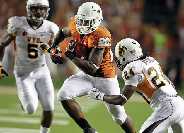 Malcolm Brown slants toward the goal line between Korey Jones (5) and Kenny Browder as Texas hosts Wyoming at D.K.Royal Stadium in Austin on September 1, 2012. Photo: Tom Reel, Express-News / ©2012 San Antono Express-News
